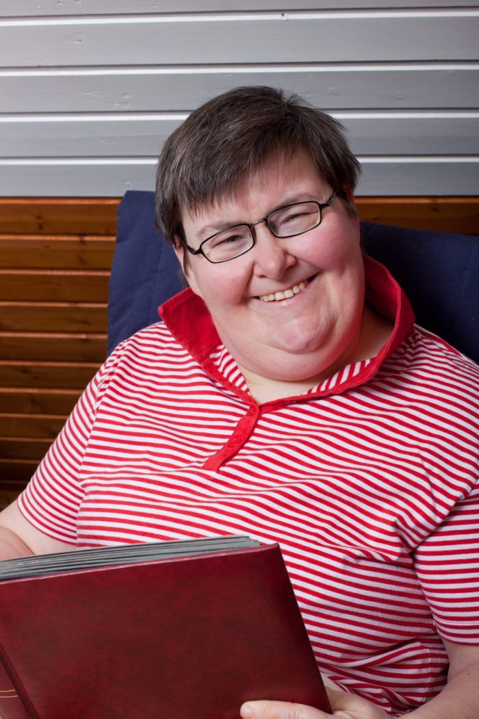 older woman with disability holds book and smiles
