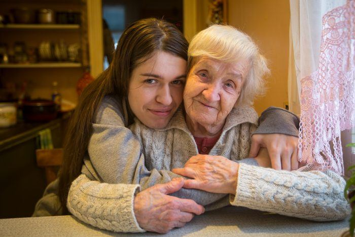 older woman being hugged by young woman