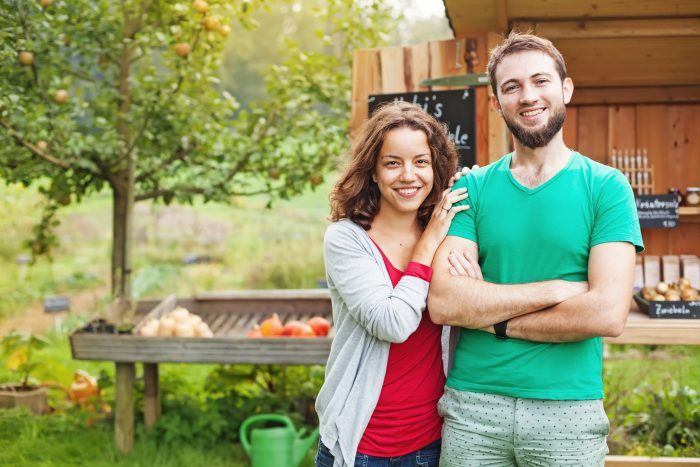 young man and woman in front of produce stand
